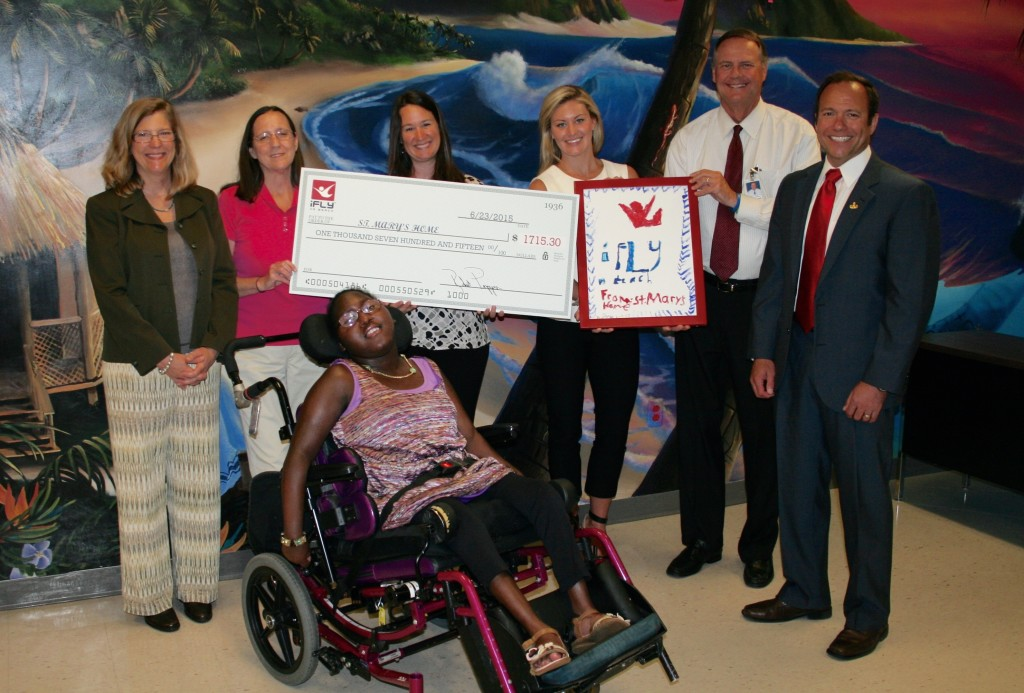"Representatives of iFLY Va Beach visited St. Mary's Home in Norfolk on June 23 to present a donation to Koko and friends that represented part of the nearly $2,200 raised during the ""Soar with St. Mary's"" event May 30 at iFLY. Koko, 20, a resident of St. Mary's who flew during the event, presented iFLY with a piece of artwork painted by Jorge, another resident who also flew. With Koko are, from left: Mary Helen Hilton, St. Mary's director of annual giving; Rhonda Bailey, PTA, St. Mary's director of physical therapy; Shannon Edsall, St. Mary's development associate; Renée Ainslie-Rodriguez, iFLY Va Beach marketing & public relations manager; William C. Giermak, St. Mary's CEO; and Bob Pizzini, iFLY Va Beach CEO."
