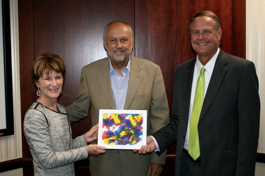 Gary Lisota, president and CEO of Valkyrie Enterprises, LLC, center, accepts a piece of artwork created by 14-year-old Aidan, a family friend who lives at St. Mary's Home in Norfolk. Martha Stewart, St. Mary's director of development, and St. Mary's CEO William C. Giermak presented the artwork to Lisota on July 8, 2015, at Valkyrie's headquarters in Virginia Beach to thank the company for completing its gift to The Albero House, which opened on St. Mary's campus to care for adults with disabilities.